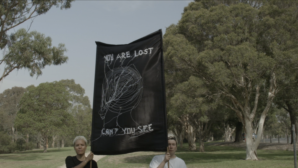 Two people hold up a banner that says 'You are lost. Can't you see?' stitched into the fabric.